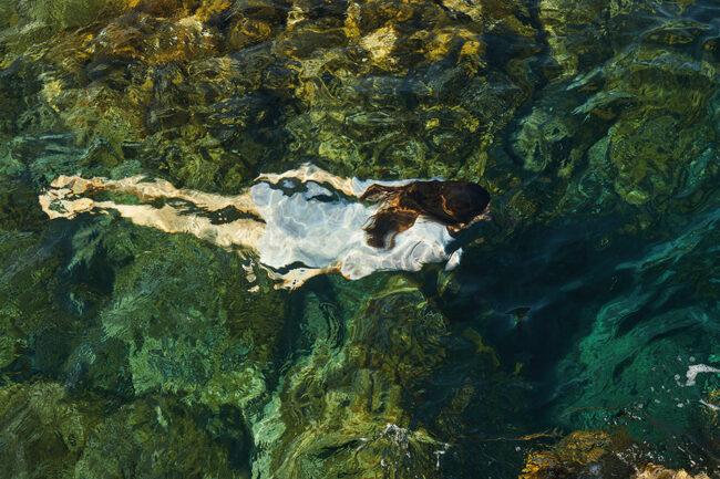 Person taucht unter Wasser in einem Kleid