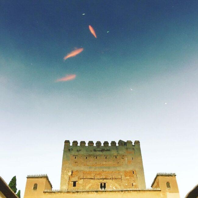 rote Fische im Himmel über einem alten Gebäude