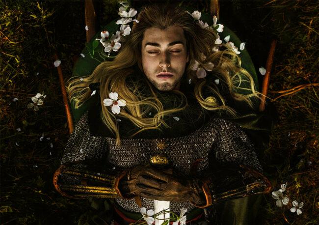 Ritter von oben fotografiert liegt mit geschlossenen Augen und hält ein Schwert
