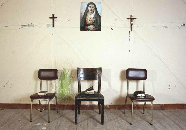 Drei Stühle mit Bibeln und Kreuzen an der Wand