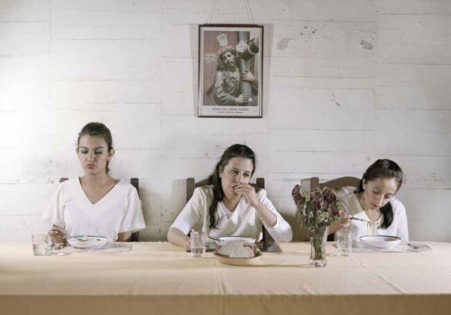 Drei Frauen sitzen geschmink an einem Esstisch