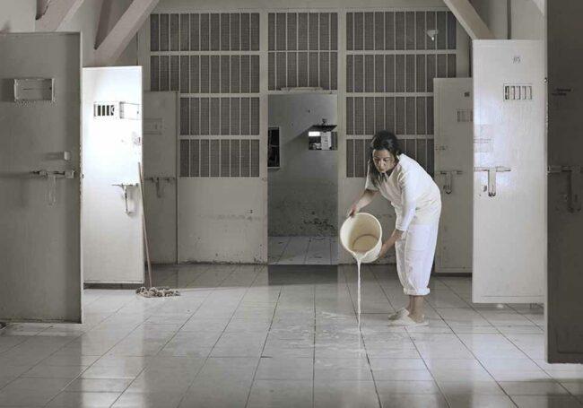 Frau leert einen Eimer Wasser auf Fließen aus