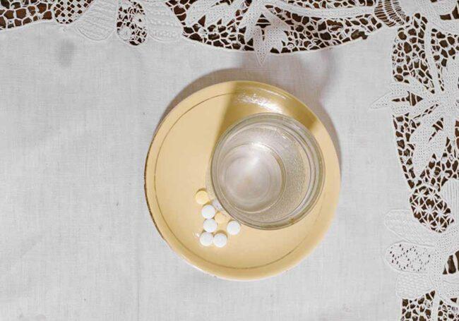 Tabletten und ein Glas Wasser