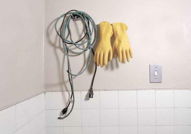 Gummihandschuhe und Seil an einer gekachelten Wand