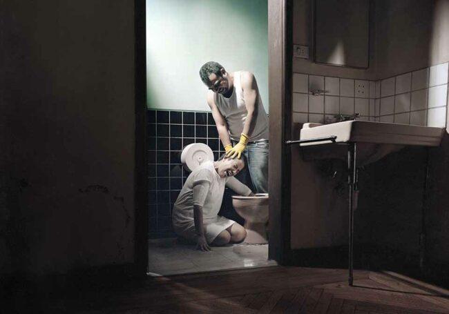 Mann foltert Frau und hält ihren Arm in eine Toilette