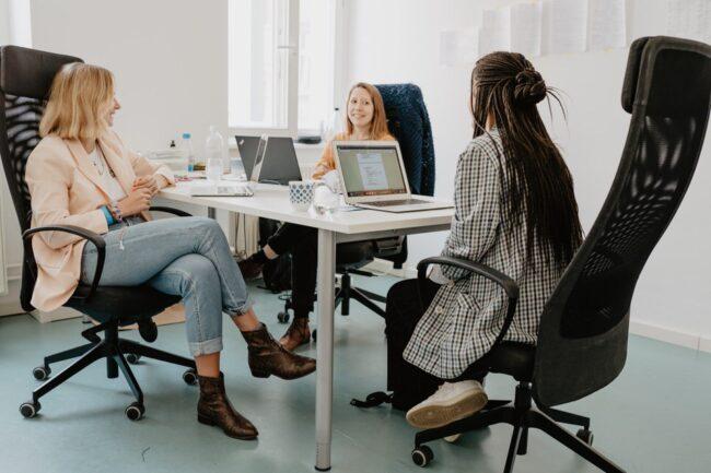 Drei Frauen an einem Bürotisch