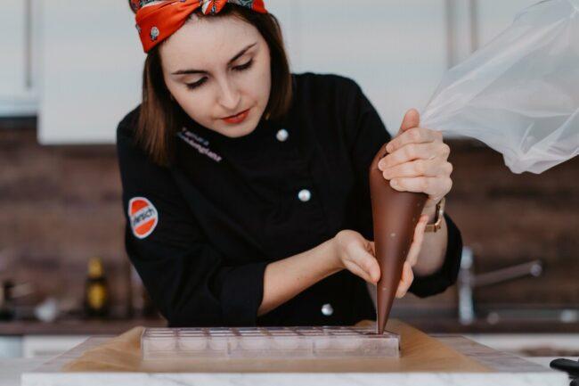 Frau mit Spritzbeutel füllt schokolade in Behälter
