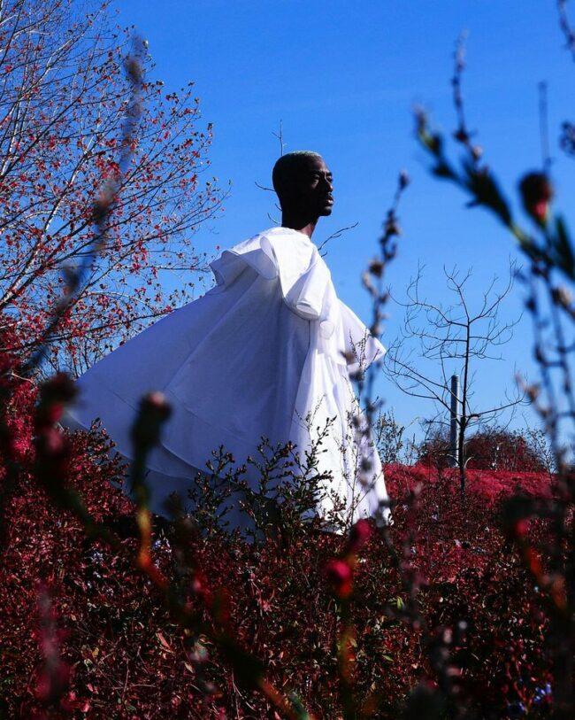 Person in wallendem Kleid in der Natur