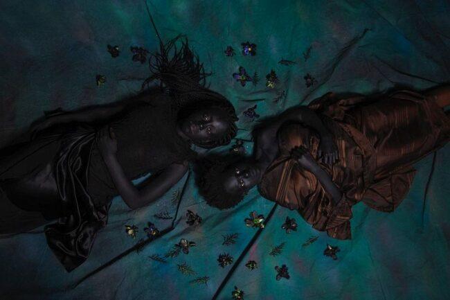 zwei Personen liegen im Dunkeln auf dem Boden