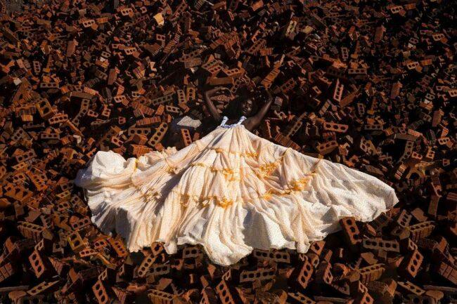 Person liegt mit ausgebreitetem Kleid auf einer Fläche aus Ziegelsteinen