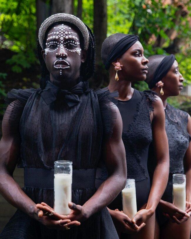 drei Personen tragen Kerzen