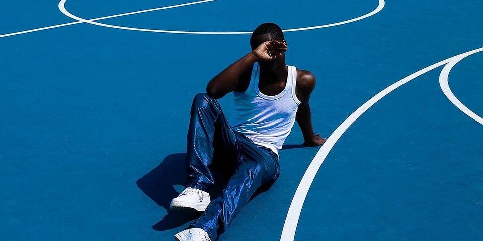 Person in blauer Hose und Unterhemd auf blauem Sportplatz