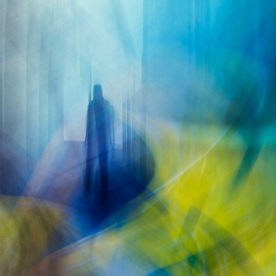 Silhouette einer Person zwischen blauen und gelben Schemen