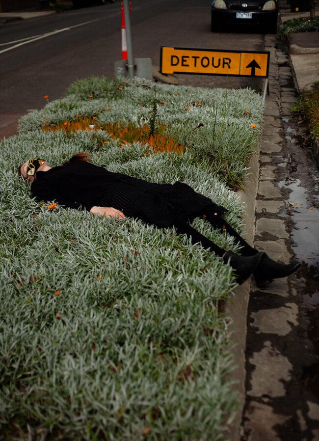 Person liegt im Grünstreifen