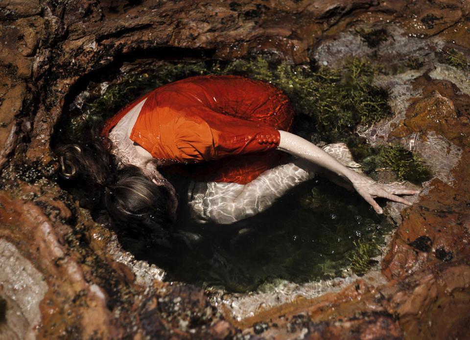 Person kauert in Wasserloch