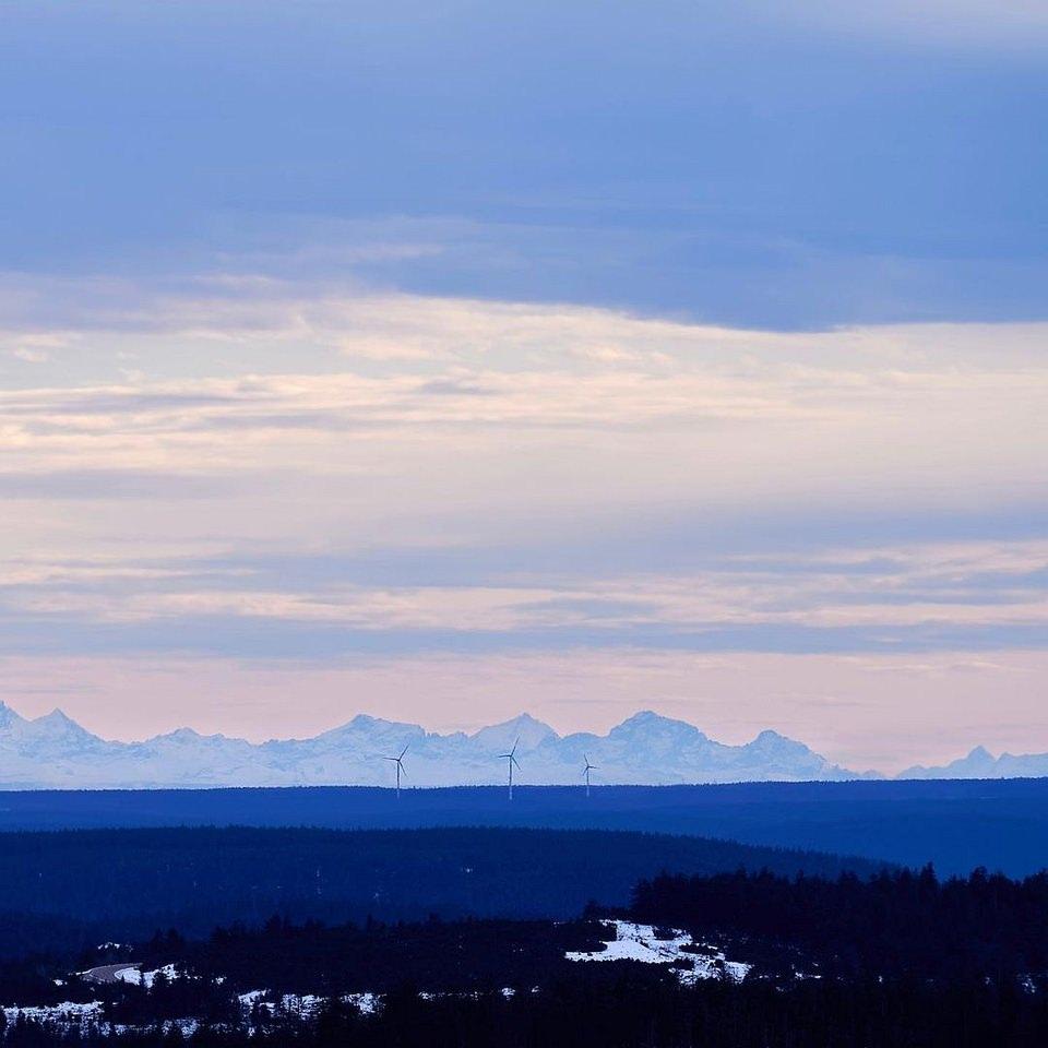 weite Landschaft vor Bergen mit Windrädern