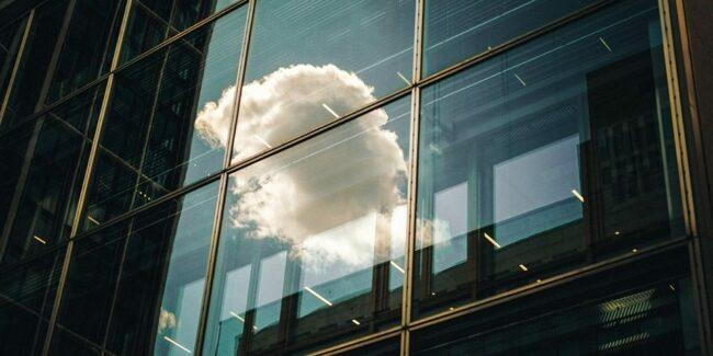 Spiegelung einer Wolke in einer Glasfassade