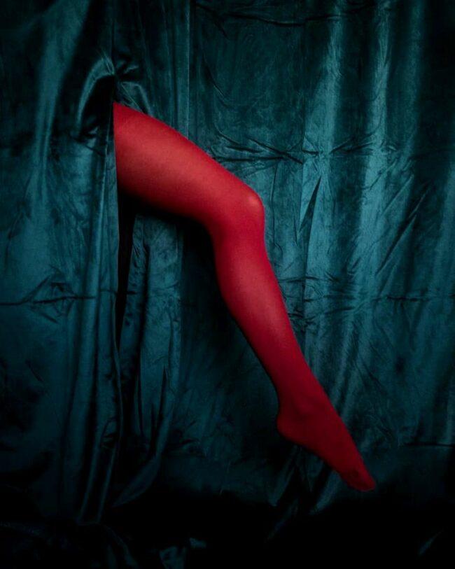 Bein in roter Strumpfhose zwischen blauem Samt