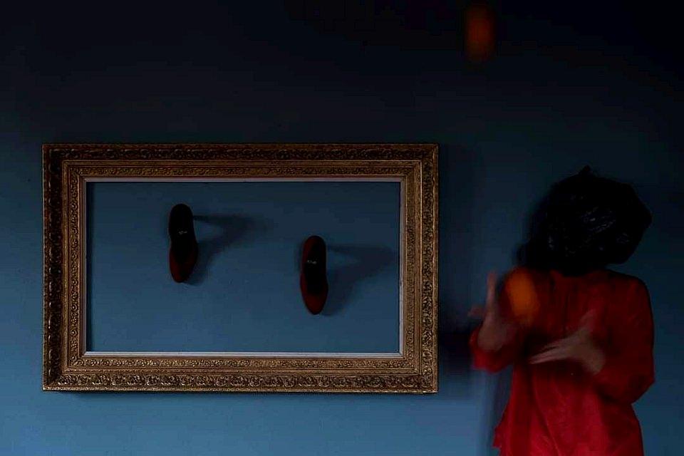 Person in rotem Kleid vor blauer Wand mit großem Bilderrahmen