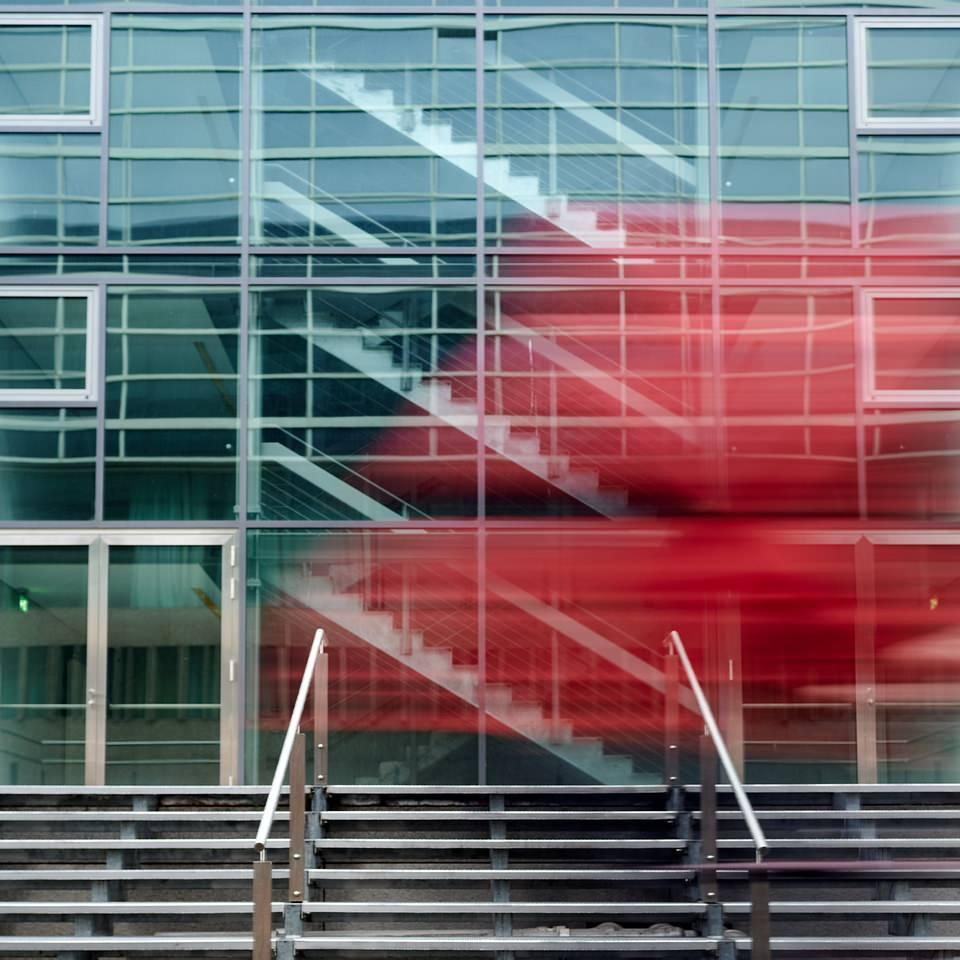 rot verwischt vor Glasfassade