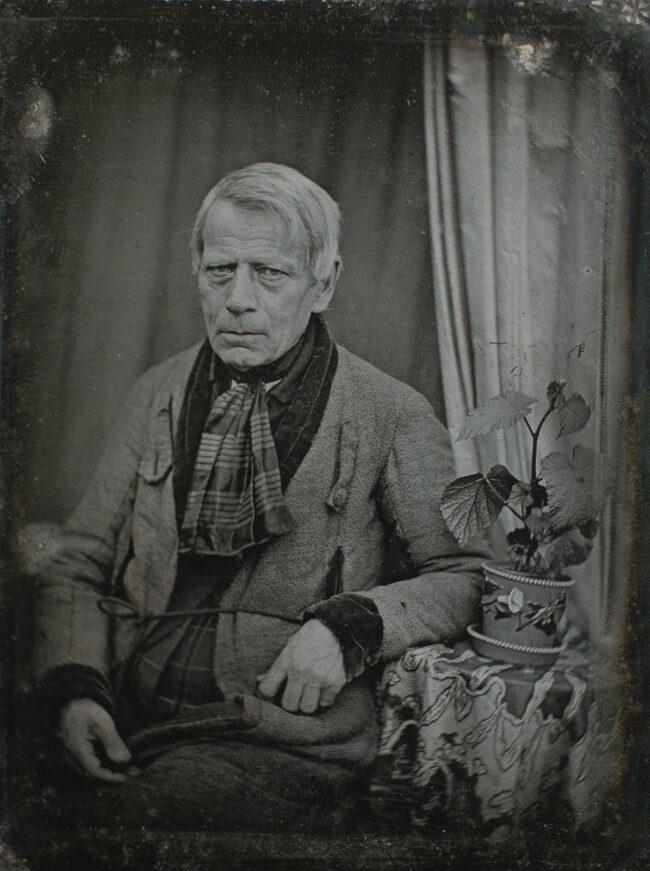 altes Männerportrait mit Pflanze