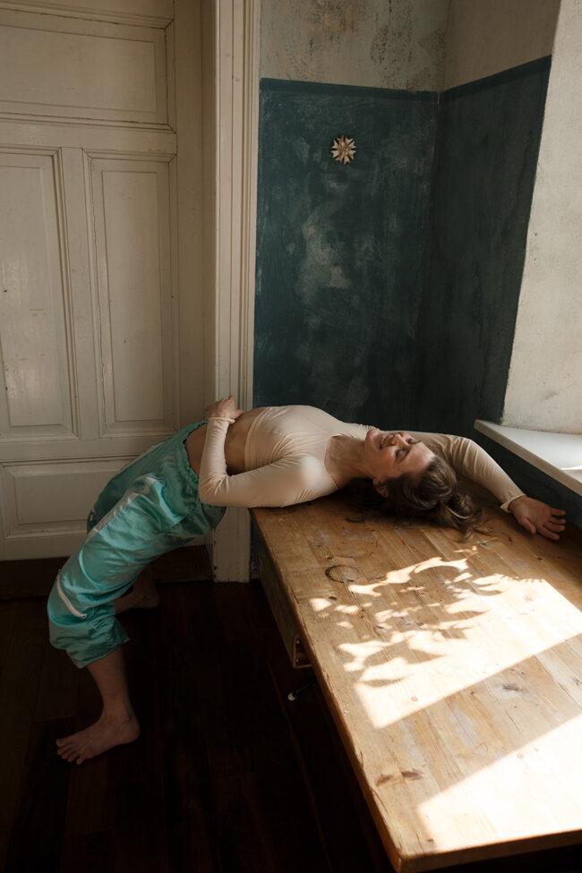 Frau liegt über einem Tisch