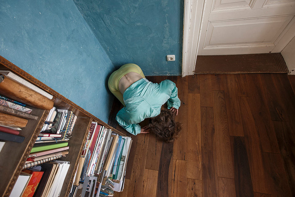 Person kauert in einer Zimmerecke