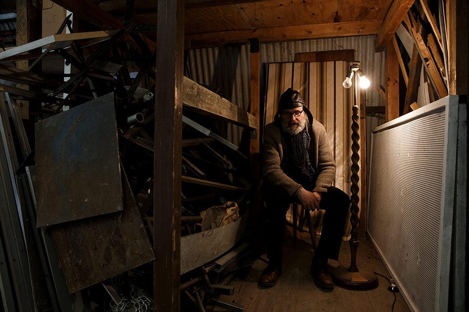 Mann sitzt in einer Ecke mit Lampe