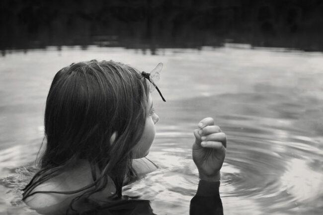 Kind im Wasser mit Libelle auf der Stirn