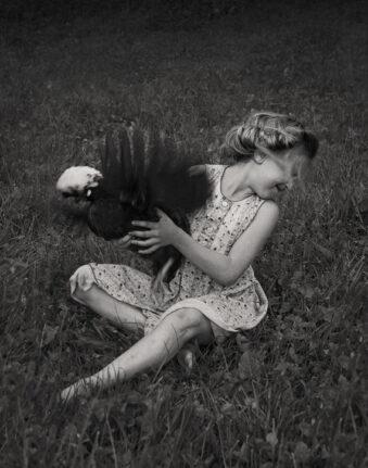 Mädchen mit flatterndem Huhn im Arm