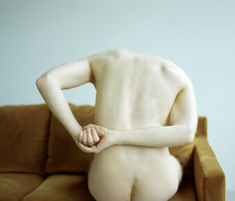 Mann sitzt mit dem Rücken zur Kamera auf einem Sofa