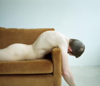 nackter Mann über ein Sofa gebeugt