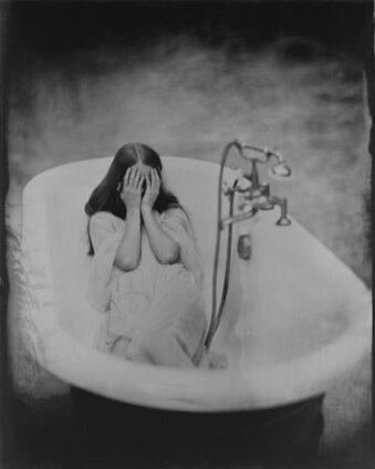 Frau mit verschränkten Händen vor dem Gesicht in einer Badewanne