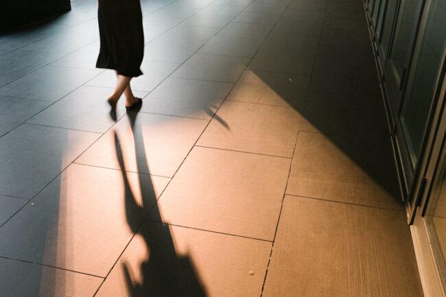 Person läuft über lichtbeschienenen Boden