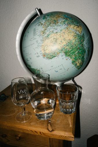 Vase und Gläser vor Globus