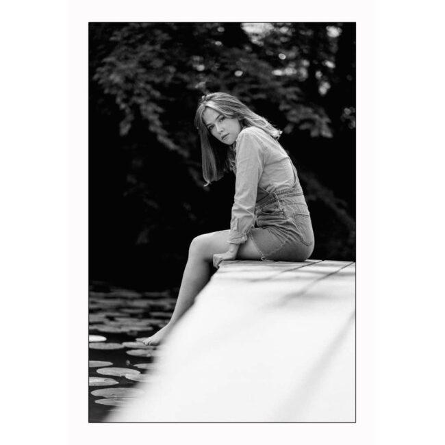 Frau sitzt an einem Teich