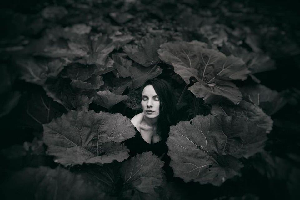 Frau zwischen großen Blättern