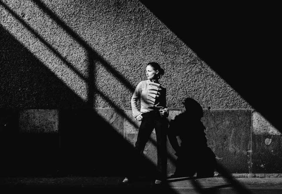 Frau an einer Wand mit Schattenspielen