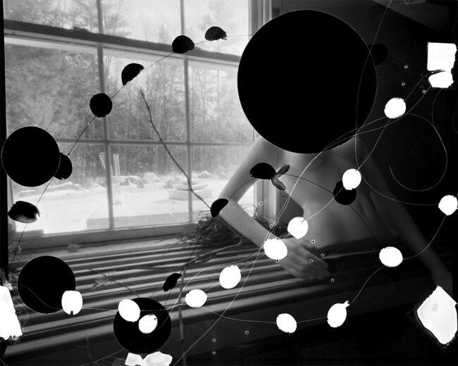 Schwarzweißfoto mit Kreisen auf einer Schaufensterpuppe vor einem Fenster