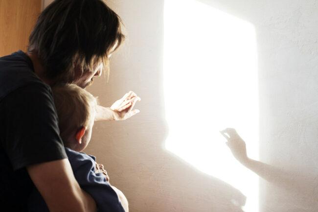 Vater macht Schattenspiele für Kind
