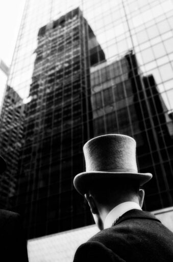 Mann mit Zylinder vor Wolkenkratzer
