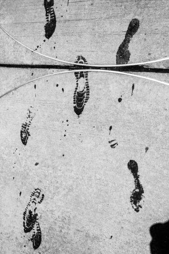 Nasse Fußspuren auf grauem Boden