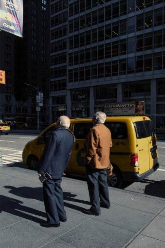 Zwei Menschen vor einem gelben Auto
