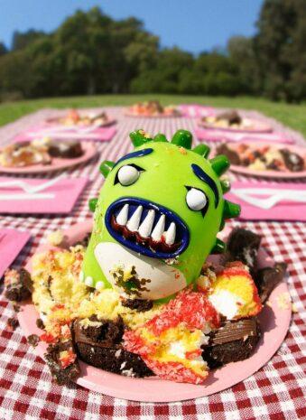 Spielzeugfigur auf einem Teller mit Kuchen beim Picknick