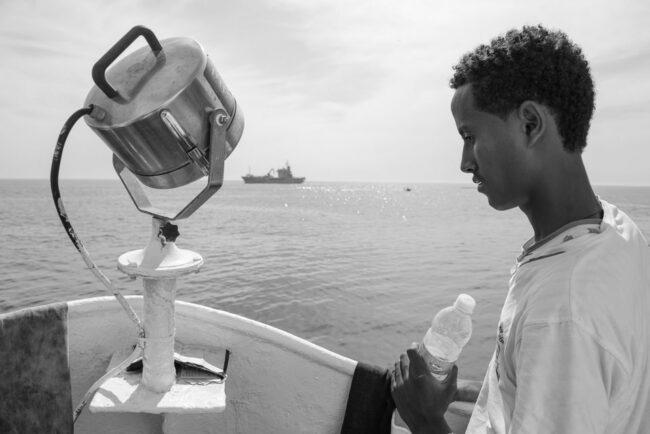 Mann mit Wasserflasche auf einem Boot