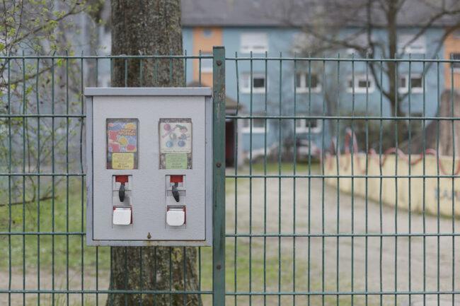Kaugummiautomat an einem Zaun