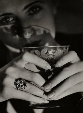 Frau hält sich mit beiden Händen einen Trinkkelch vors Gesicht