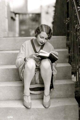 Eine Frau sitzt auf einer Treppe und gibt den Blick auf ihre Unterwäsche frei