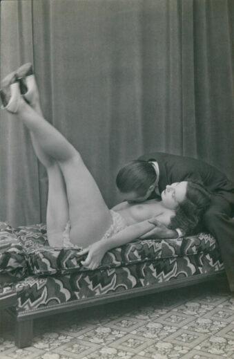 Frau liegt nackt auf einem Sofa, ein Mann beugt sich zu ihr hinunter