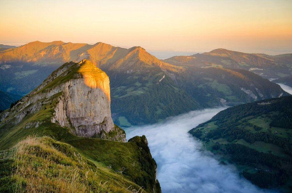 Blick nach unten auf ein Tal voller Nebel